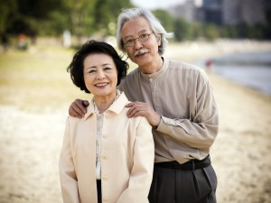 Elderly Asian couple pose together on a beach and smile at the camera.